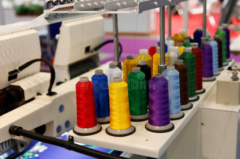 Colored thread cones on stand attachment stock photos