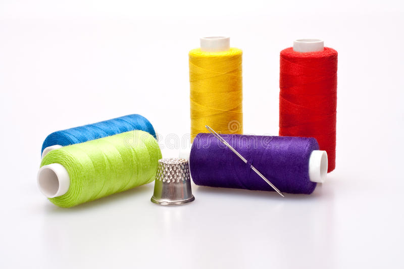 Colored thread for sewing with needle and thimble royalty free stock photo