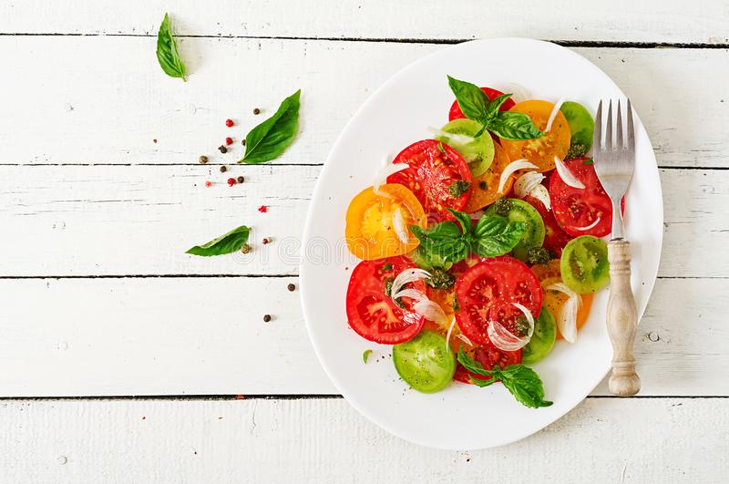 Colored tomato salad with onion and basil pesto. royalty free stock photography