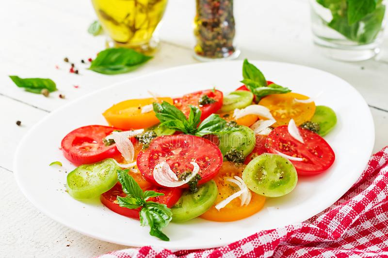 Colored tomato salad with onion and basil pesto. royalty free stock images