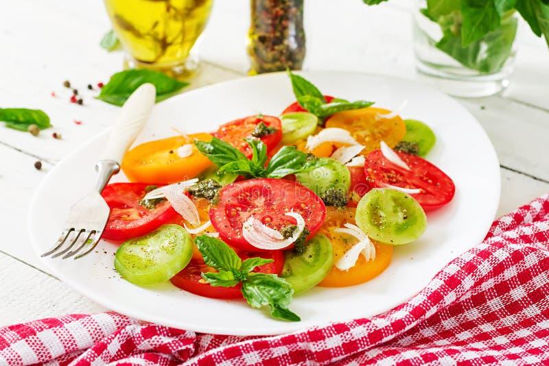 Colored tomato salad with onion and basil pesto. stock photos