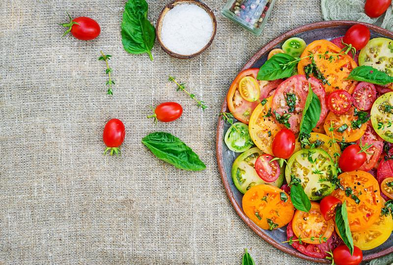 Colored tomato salad with onion and basil. Vegan food. royalty free stock image