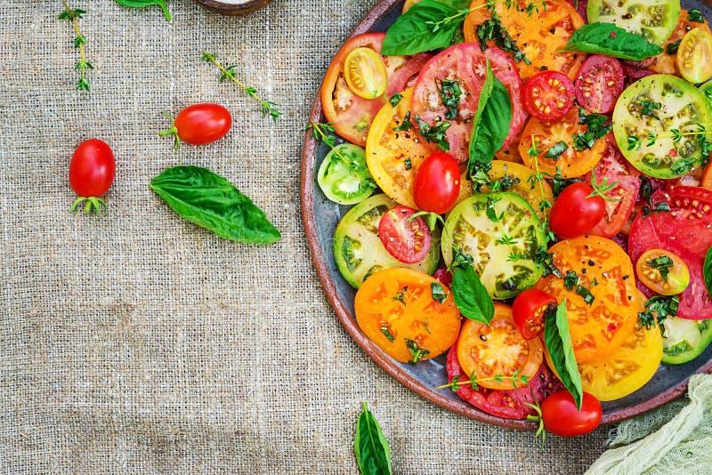 Colored tomato salad with onion and basil. Vegan food. stock image