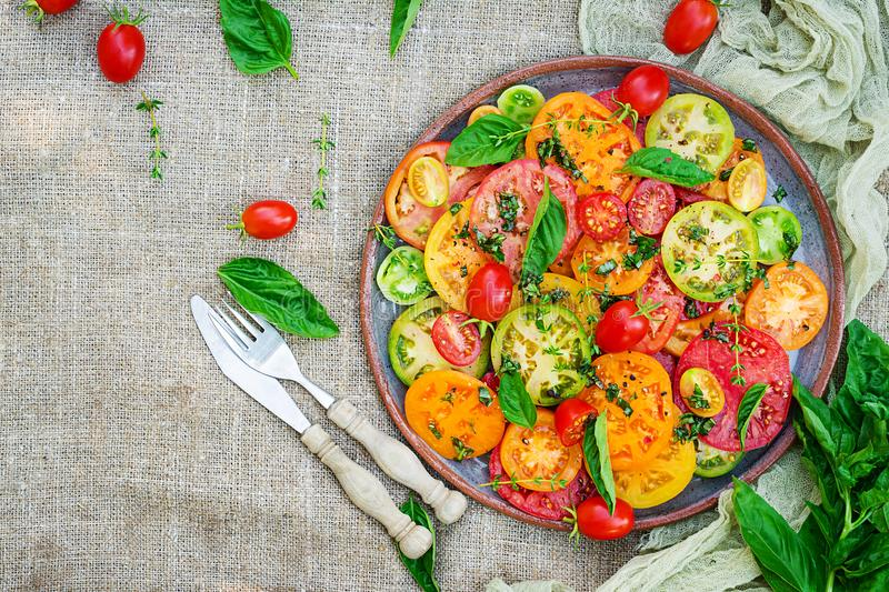 Colored tomato salad with onion and basil. Vegan food. royalty free stock photography