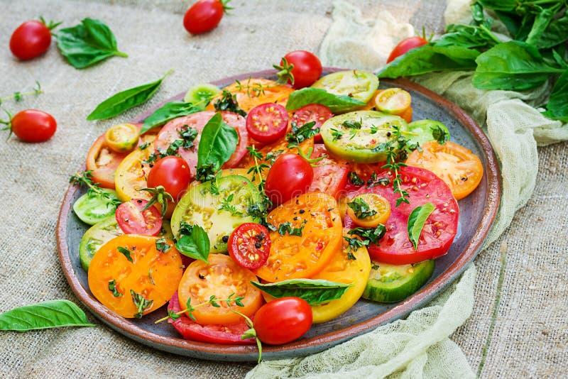 Colored tomato salad with onion and basil. Vegan food. stock photography