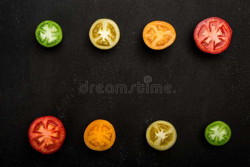 Colored tomatoes cut in half at the top and bottom of the frame. Fresh vegetables, copy space royalty free stock images
