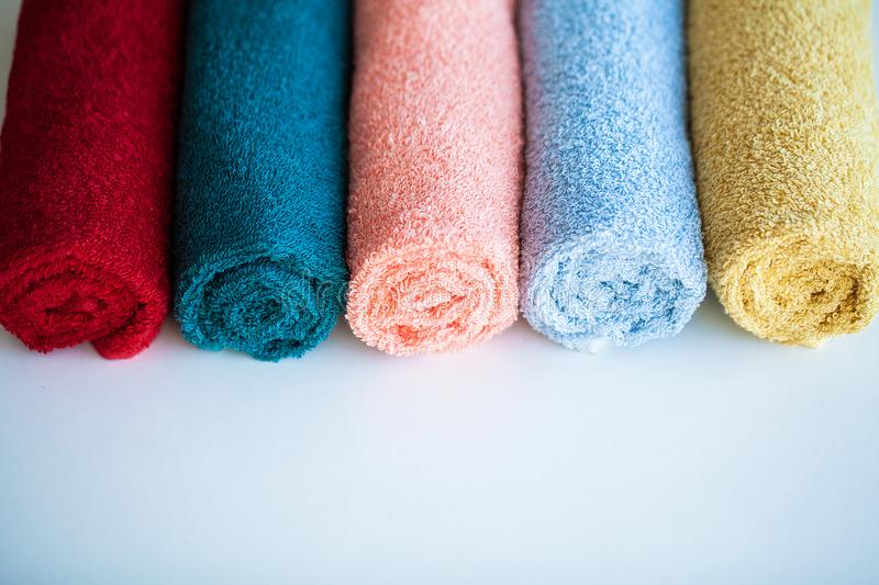 Colored towels on white table with copy space on bath room background. royalty free stock images