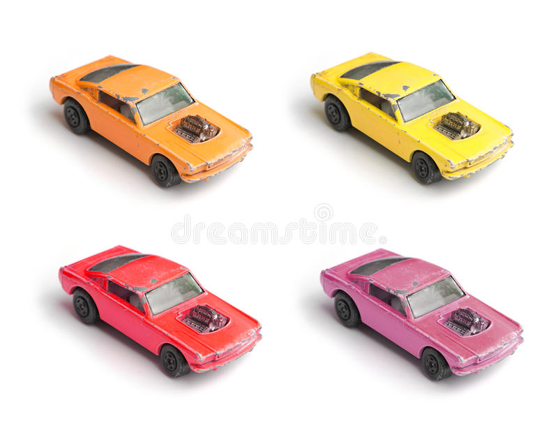 Colored toy car miniature models. Four colored miniature cars of the same type isolated on a white background royalty free stock photo
