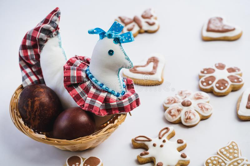Colored toy chicken and painted chicken easter eggs in a wicker nest and gingerbread cookies, covered with white and chocolate ici. Ng-sugar, on a white table royalty free stock images