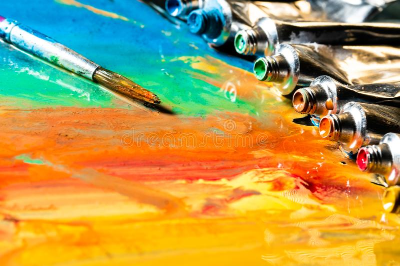 Colored tubes with paintbrush on the painted canvas background. Creative colored wallpaper. Open colored tube on floor. Painted su royalty free stock photos