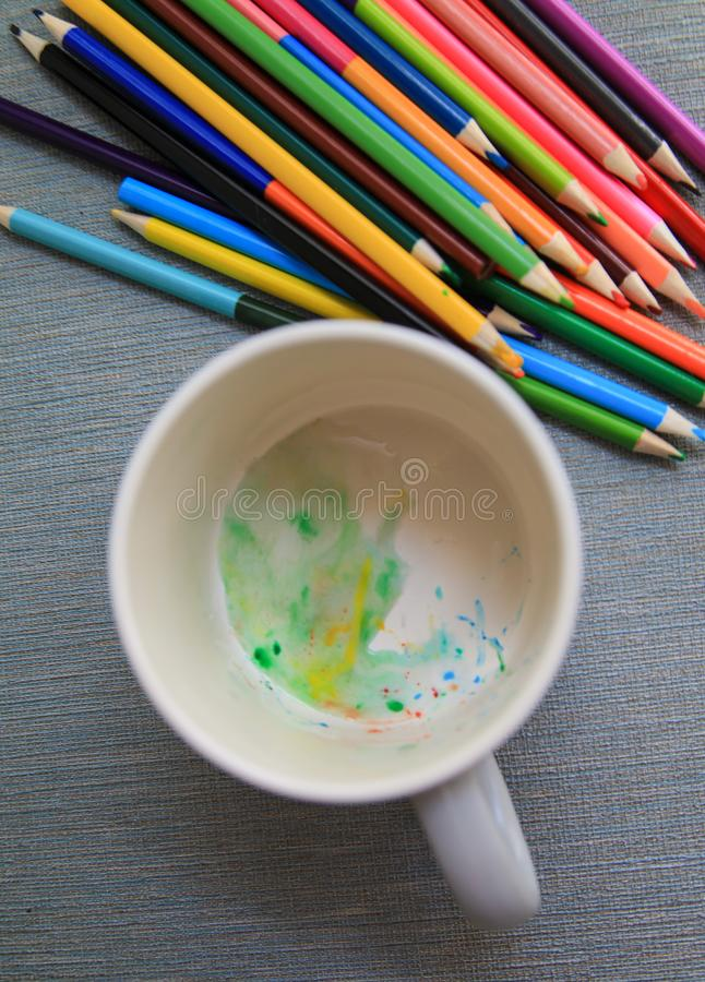 Colored watercolor pencils in a mug. Colorful water drops. Creation stock photography