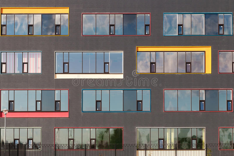 Colored windows of the building with the sky reflected in the glass. Geometric background. Building`s facade. Colored windows of the building. geometric royalty free stock image