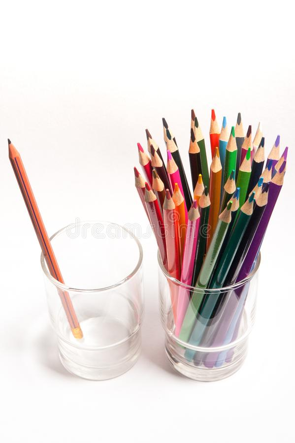 Colored wood pencils in front of simple graphite pencil on table in glasses isolated stock photo