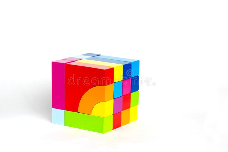 Colored wooden blocks, cubes, build on a light white background. A cube of colored wooden details. Colored wooden blocks, cubes, build on a light white stock photos
