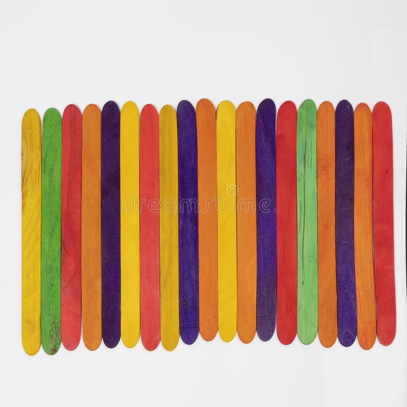 Colored wooden slats. Some colored wooden slats arranged on a white surface stock images