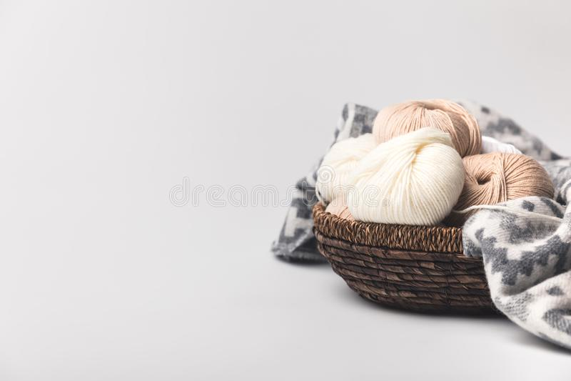 Colored yarn balls in wicker basket with blanket. Isolated on white royalty free stock photo