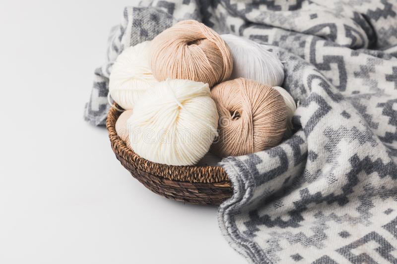 Colored yarn balls in wicker basket with blanket. Isolated on white royalty free stock image