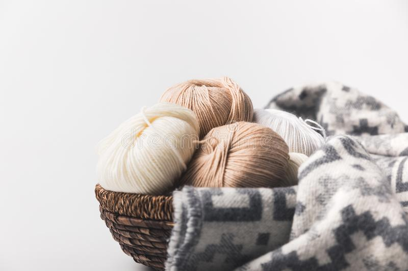 Colored yarn balls in wicker basket with blanket. Isolated on white royalty free stock images
