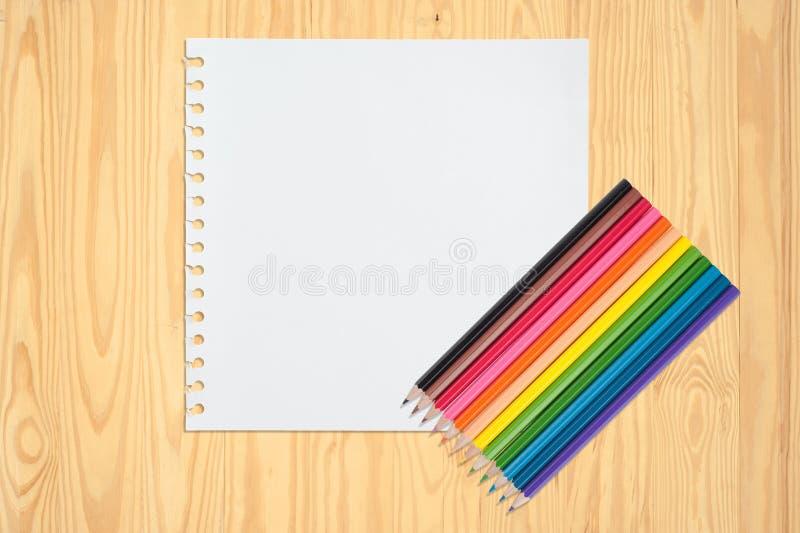 Coloree el lápiz en el libro del bosquejo y la tabla de madera del vintage para el fondo y el texto foto de archivo