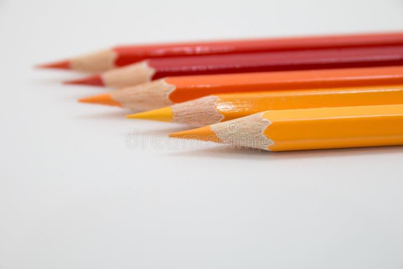 Coloree el tono caliente de los lápices en el fondo blanco fotografía de archivo