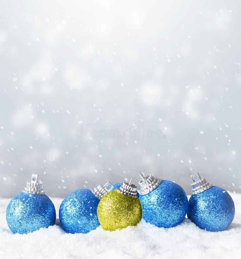 Coloree las bolas brillantes de la Navidad en fondo de la nieve fotos de archivo