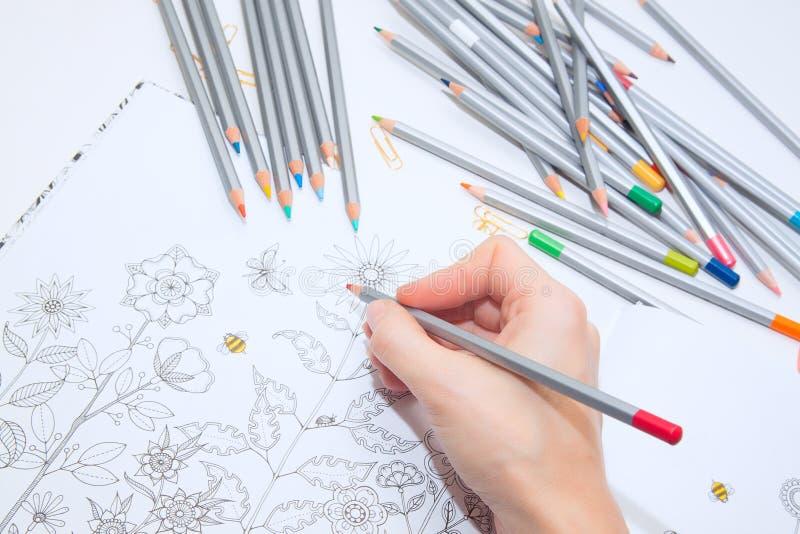 Colorer - αντιαγχωτικό με τα χρωματισμένα μολύβια Το κορίτσι χρωματίζει ένα χρωματίζοντας βιβλίο για τους ενηλίκους με τα κραγιόν στοκ εικόνα