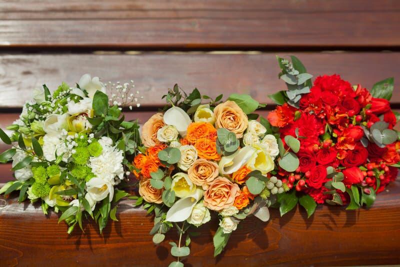 Colores blancos, anaranjados y rojos del ramo de tres bodas - imagenes de archivo