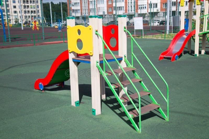 Colores brillantes de madera de la diapositiva en el patio con la capa recubierta de goma foto de archivo libre de regalías