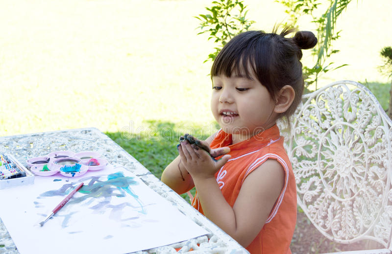 Colores de agua de la pintura de la niña en jardín en casa fotografía de archivo libre de regalías