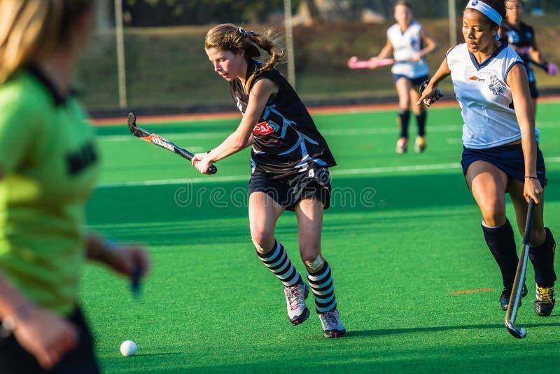 Colores de la acción de la bola del palillo de las muchachas del hockey foto de archivo
