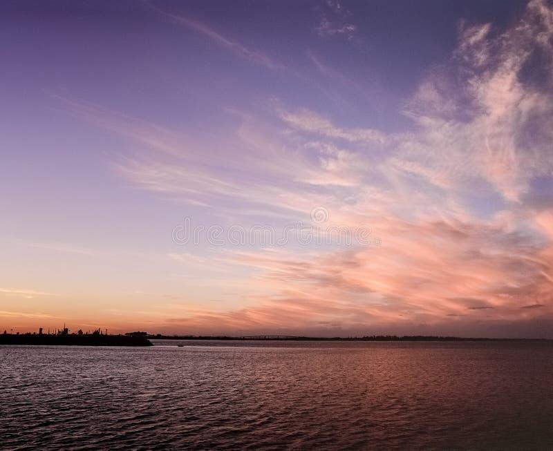 Colores de la puesta del sol en nubes sobre del agua del océano del puerto de Newcastle Nuevo Gales del Sur Australia del día aná fotos de archivo libres de regalías