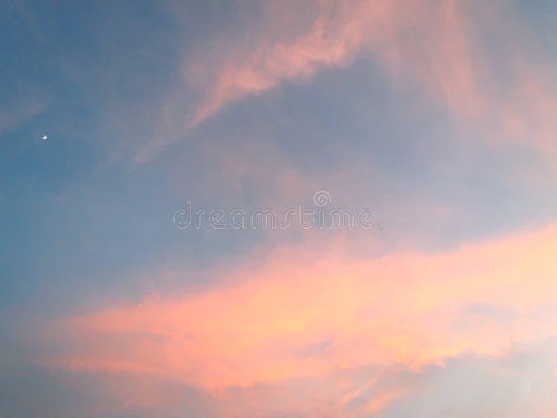 Colores del cielo y de las nubes antes de la puesta del sol/de la salida del sol con la luna en el cielo imagen de archivo