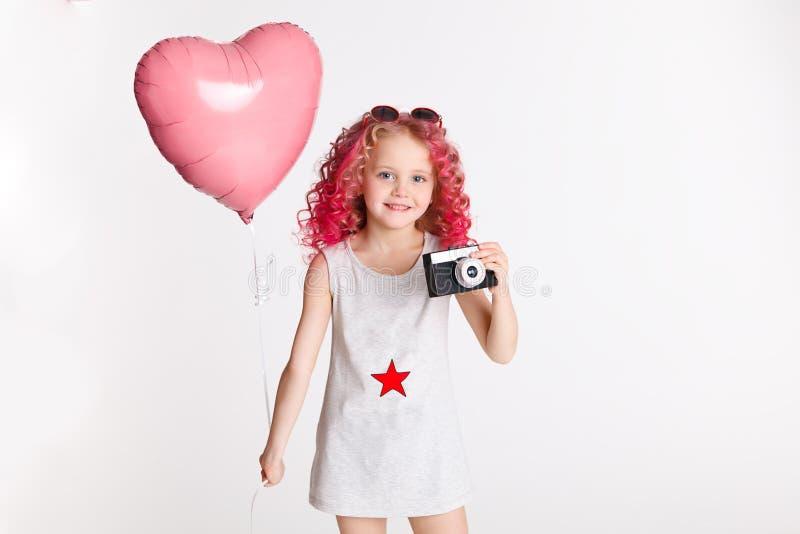 Colores-Haare Porträt des lustigen Modehippie-Mädchens mit rosa Ballon in Form des Herzens Retro- Kamera in ihrer Hand stockfotos