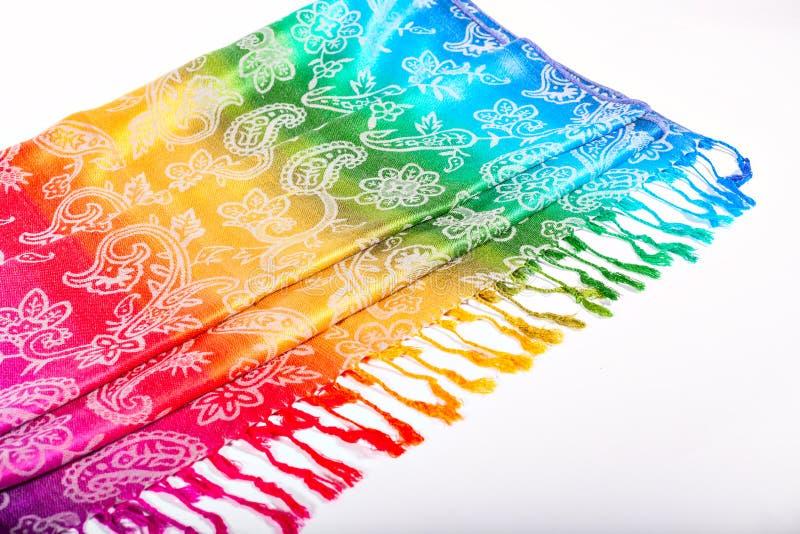 Colores indios del arco iris de la bufanda con los cepillos en un fondo blanco imágenes de archivo libres de regalías