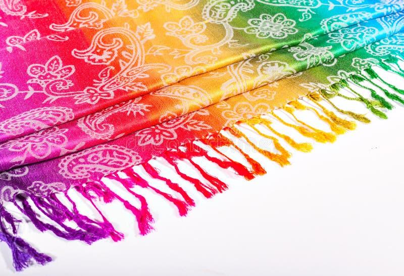 Colores indios del arco iris de la bufanda con los cepillos en un fondo blanco imagen de archivo