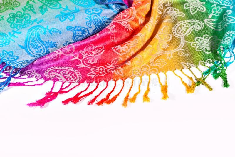Colores indios del arco iris de la bufanda con los cepillos en un fondo blanco fotos de archivo