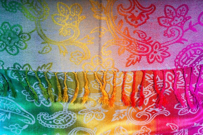 Colores indios del arco iris de la bufanda con los cepillos en un fondo blanco fotografía de archivo libre de regalías