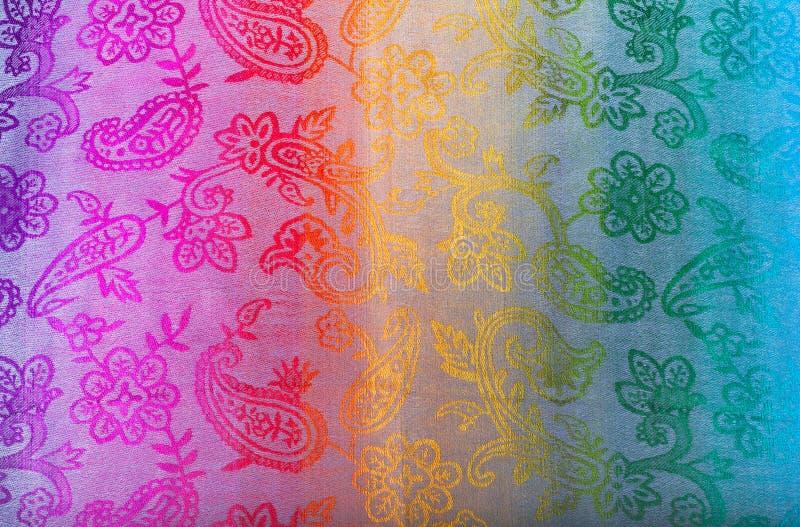 Colores indios del arco iris de la bufanda con los cepillos en un fondo blanco foto de archivo libre de regalías