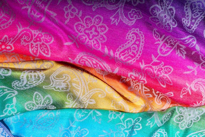Colores indios del arco iris de la bufanda con los cepillos en un fondo blanco fotografía de archivo