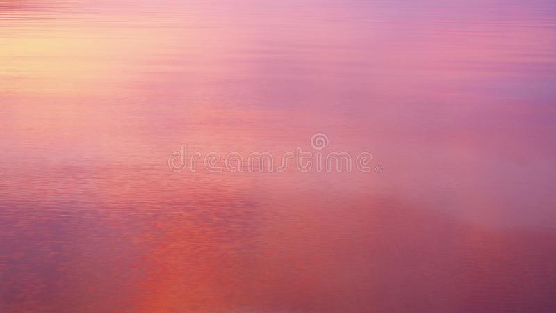 Colores intensos de la salida del sol reflejados en agua de mar tranquilo imagenes de archivo