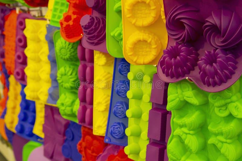 Colores y formas del bakeware del silicón los diversos cuelgan en el estante imágenes de archivo libres de regalías
