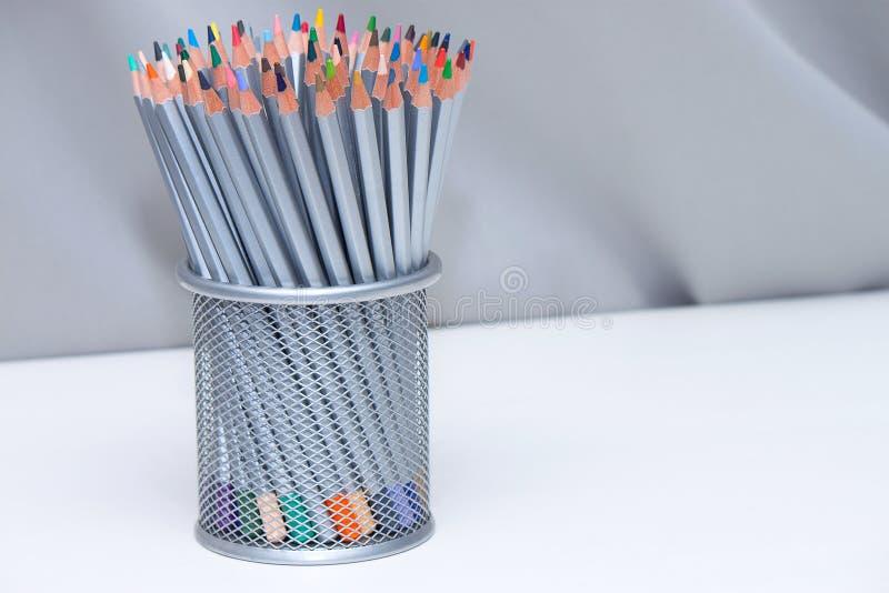 Colorez les crayons dans le busket sur la table blanche en bois avec le fond gris photos stock