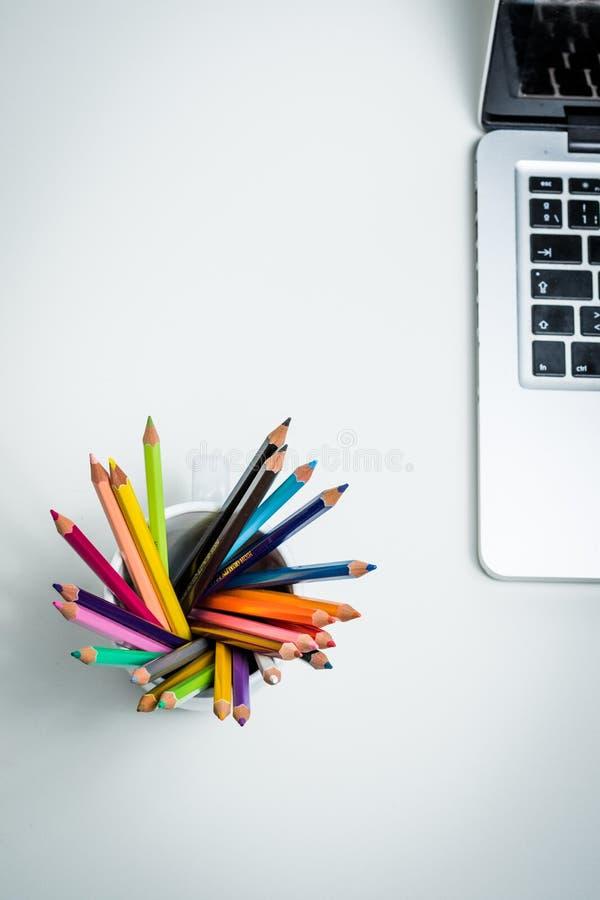 Colorez les crayons dans une tasse blanche et un ordinateur portable photos libres de droits