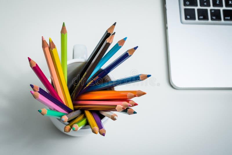 Colorez les crayons dans une tasse blanche et un ordinateur portable photo libre de droits