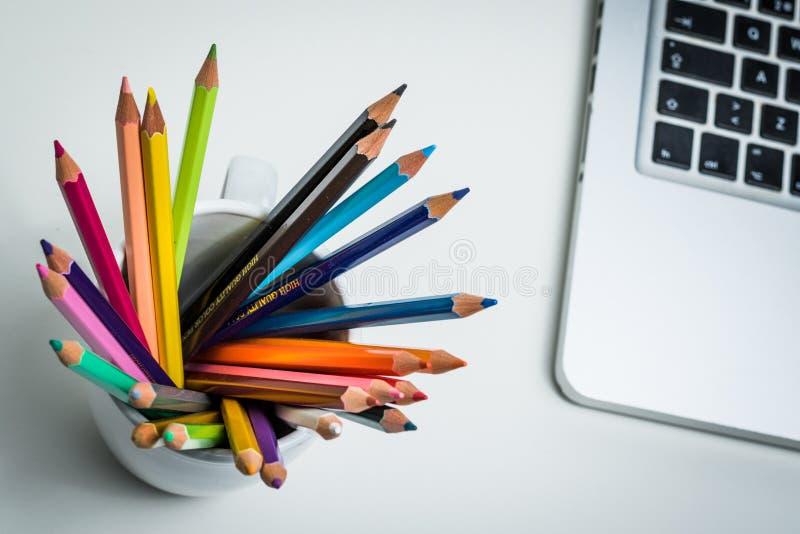 Colorez les crayons dans une tasse blanche et un ordinateur portable images libres de droits