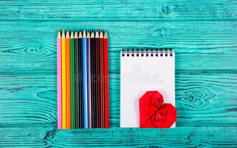 Colorez les crayons, le carnet et le coeur de l'origami sur un fond bleu Accessoires de papeterie image libre de droits