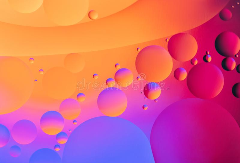 Colorful abstract background. Orange pink purple blue circles and oil bubbles in the water close-up. Macro abstraction stock photos