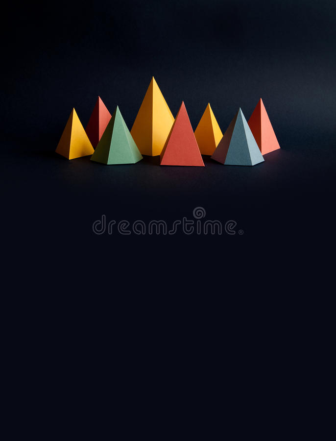Colorful abstract geometric shape figures still life. Three-dimensional pyramid prism rectangular cube on black blue. Background. Yellow blue pink malachite stock images
