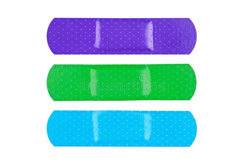 Colorful adhesive bandages. Three colorful adhesive bandages isolated on white royalty free stock photo