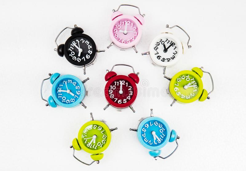 The colorful alarm clocks put on white background stock photos
